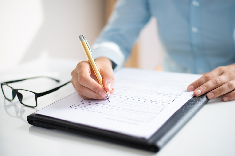 Closeup of business woman making notes in document. Entrepreneur sitting at desk and writing. Paperwork concept. Cropped view.